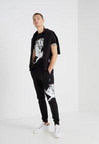 Plein Sport - JOGGING TROUSERS CROSS TIGER - Pantalon de survêtement - black - 1