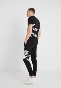 Plein Sport - JOGGING TROUSERS CROSS TIGER - Pantalon de survêtement - black - 2