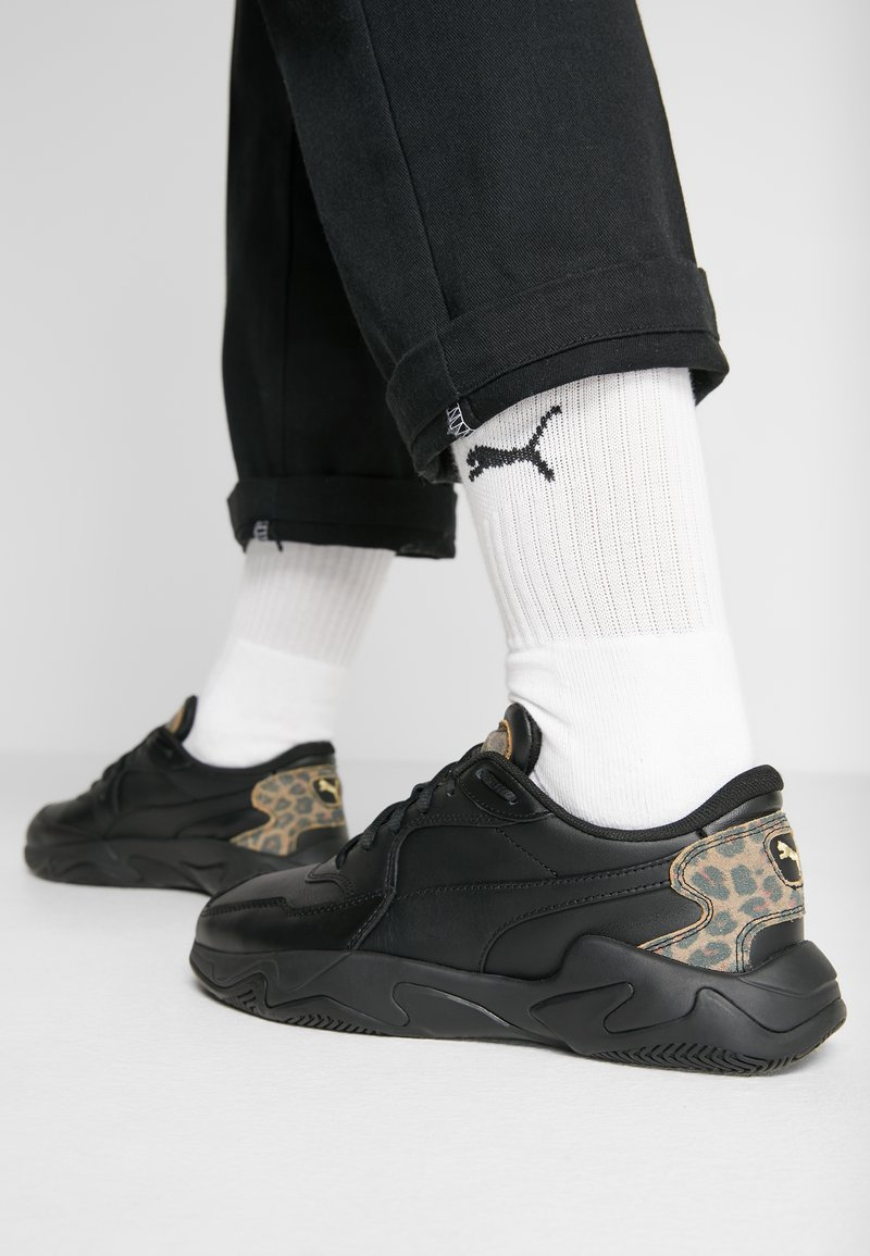 Puma - STORM LEO - Sneakers laag - black/team gold