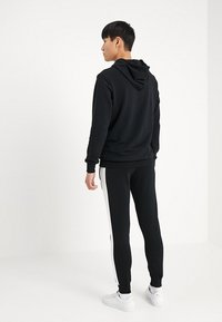 Puma - ICONIC TRACK PANTS - Pantalon de survêtement - black - 2
