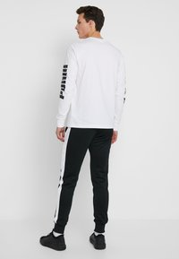 Puma - ICONIC TRACK PANT CUFF - Pantalon de survêtement - black - 2