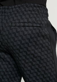 Puma - LUXE PACK TRACK PANTS - Träningsbyxor - black - 3