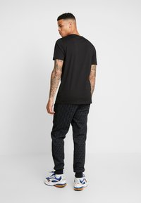 Puma - LUXE PACK TRACK PANTS - Träningsbyxor - black - 2