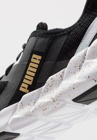 Puma - WEAVE XT METAL - Sportovní boty - black/metallic gold - 5