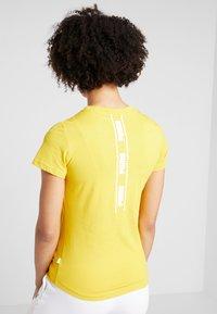 Puma - AMPLIFIED TEE - Print T-shirt - sulphur - 2
