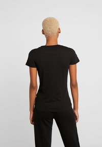 Puma - AMPLIFIED TEE - T-shirt con stampa - black - 2