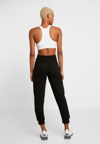 Puma - AMPLIFIED PANTS  - Trainingsbroek - black - 2