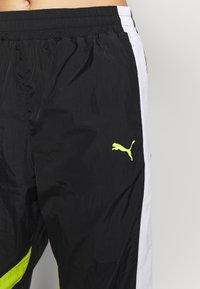 Puma - STUDIO CLASH ACTIVE TRACK PANTS - Teplákové kalhoty - black - 5