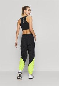 Puma - STUDIO CLASH ACTIVE TRACK PANTS - Teplákové kalhoty - black - 2