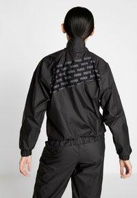 Puma - FEEL IT - Training jacket - puma black - 2