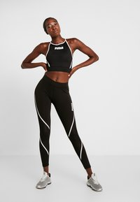 Puma - PAMELA  REIF X PUMA CROP TOP - Sports shirt - black - 1