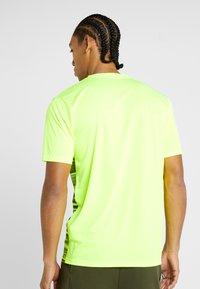 Puma - FTBLNXT GRAPHIC CORE - T-shirt med print - yellow alert/grey dawn - 2