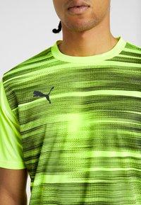Puma - FTBLNXT GRAPHIC CORE - T-shirt med print - yellow alert/grey dawn - 5