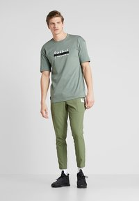 Puma - CASUAL PANTS - Träningsbyxor - olivine/charcoal gray - 1