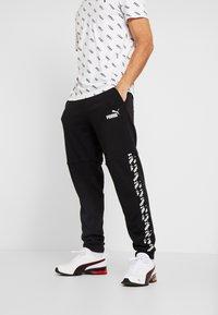 Puma - AMPLIFIED PANTS - Pantalon de survêtement - puma black - 0