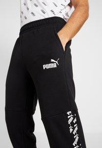 Puma - AMPLIFIED PANTS - Pantalon de survêtement - puma black - 4