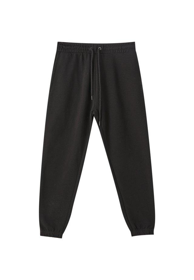 MIT GUMMIZUG AM SAUM - Spodnie treningowe - black