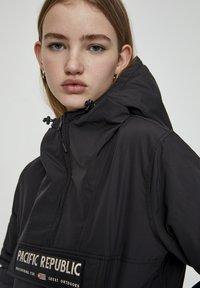 PULL&BEAR - MIT BAUCHTASCHE UND PATCH IM KONTRAST 05713349 - Light jacket - black - 3