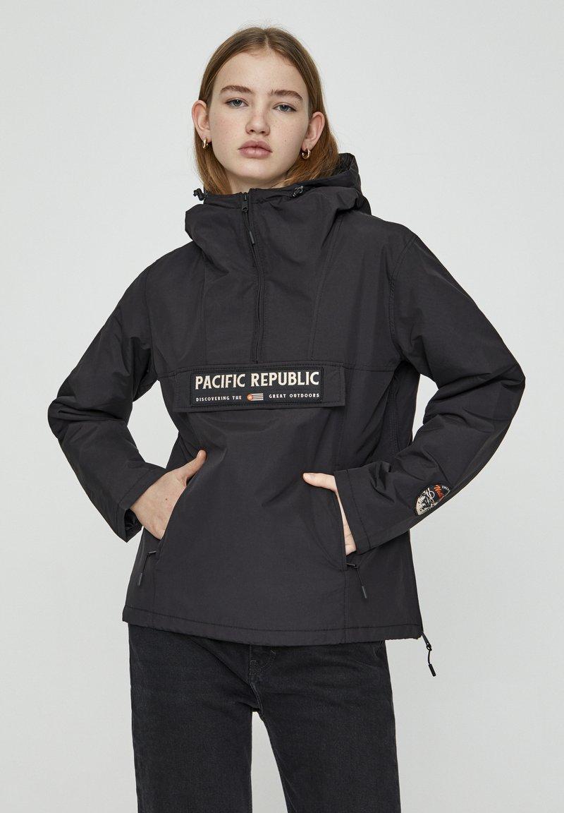 PULL&BEAR - MIT BAUCHTASCHE UND PATCH IM KONTRAST 05713349 - Light jacket - black