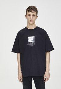 PULL&BEAR - SCHWARZES T-SHIRT MIT FARBLICH ABGESETZTEM MOTIV 09243530 - T-shirt imprimé - black - 0