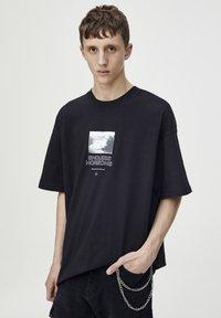 PULL&BEAR - SCHWARZES T-SHIRT MIT FARBLICH ABGESETZTEM MOTIV 09243530 - T-shirt imprimé - black - 3