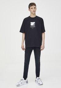 PULL&BEAR - SCHWARZES T-SHIRT MIT FARBLICH ABGESETZTEM MOTIV 09243530 - T-shirt imprimé - black - 1