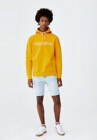 PULL&BEAR - MIT KAPUZE UND SLOGAN - Hoodie - yellow - 1