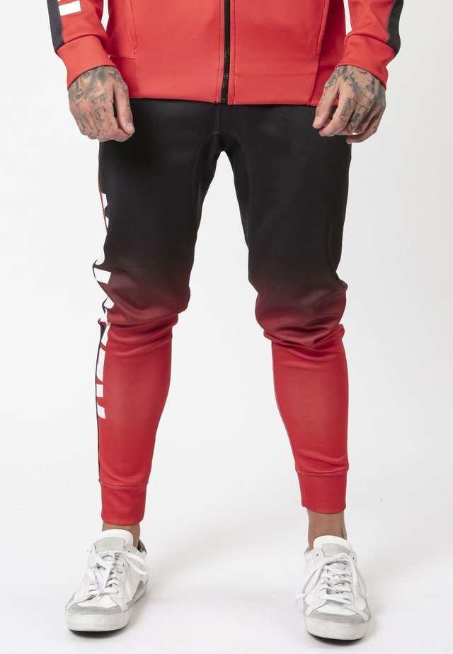 GRADIENT - Tracksuit bottoms - black/red