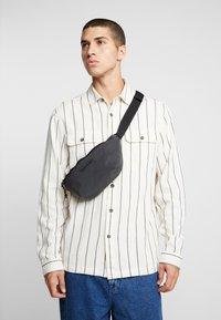 Reebok Classic - REFLECTIVE BAG - Bum bag - black - 1