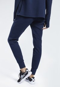 Reebok - UNITED BY FITNESS WOVEN JOGGERS - Tracksuit bottoms - collegiate navy melange - 2