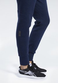 Reebok - UNITED BY FITNESS WOVEN JOGGERS - Tracksuit bottoms - collegiate navy melange - 5