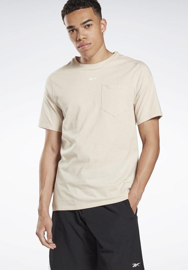 Reebok - LES MILLS® POCKET TEE - Print T-shirt - beige
