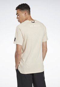 Reebok - LES MILLS® POCKET TEE - Print T-shirt - beige - 1