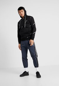Reebok - MEET YOU THERE TRAINING 7/8 JOGGER PANTS - Tracksuit bottoms - navy - 1