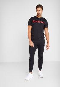 Reebok - LINEAR LOGO ELEMENTS SPORT PANTS - Pantalon de survêtement - black - 1