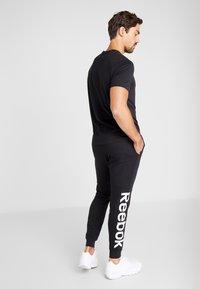 Reebok - LINEAR LOGO ELEMENTS SPORT PANTS - Pantalon de survêtement - black - 2
