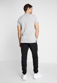 Reebok - CUFFED PANT - Pantalon de survêtement - black - 2