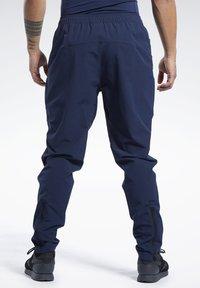Reebok - 2020-01-01 UNITED BY FITNESS TRACKSTER PANTS - Spodnie treningowe - blue - 2