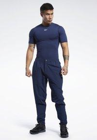 Reebok - 2020-01-01 UNITED BY FITNESS TRACKSTER PANTS - Spodnie treningowe - blue - 1