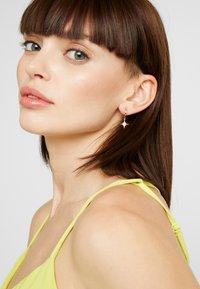 Orelia - STARBURST CHARM HUGGIE HOOPS - Earrings - gold-coloured - 1