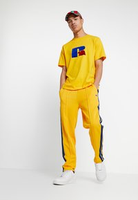 Russell Athletic Eagle R - GLAMIS STRIPED ZIP OFF TRACK PANT - Joggebukse - yellow - 1