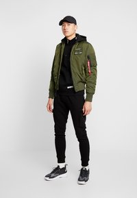 STEREOTYPE - LOW PASS - Tracksuit bottoms - black - 1