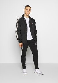 STEREOTYPE - CHROME  - Tracksuit bottoms - black - 1
