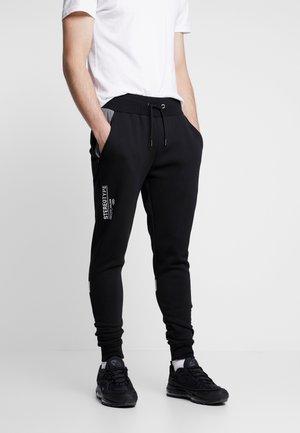 REFLECT - Teplákové kalhoty - black
