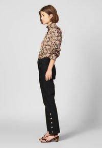 sandro - SNAPY - Jeans straight leg - black - 1