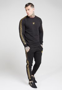 SIKSILK - MUSCLE FIT NYLON PANEL JOGGERS - Tracksuit bottoms - black/gold - 1