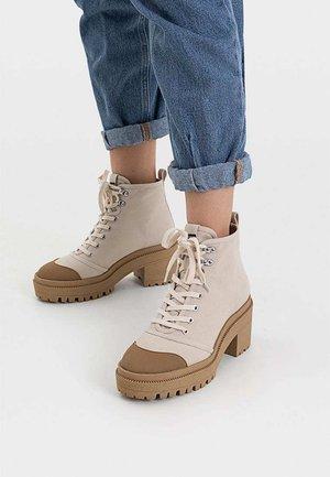 STIEFELETTEN AUS STOFF MIT ABSATZ 19409570 - Lace-up ankle boots - beige
