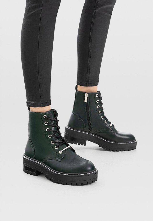 FLACHE GRÜNE STIEFELETTEN MIT DOPPELTEM SCHNÜRSENKEL 19451570 - Platform ankle boots - green