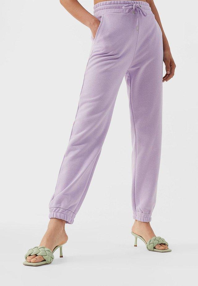 AUS PLÜSCHGEWEBE  - Tracksuit bottoms - purple