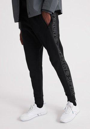 MIT STREIFENBAND - Pantalones deportivos - black